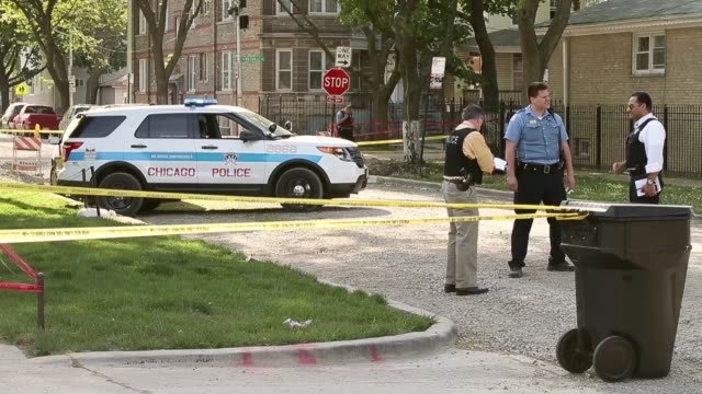 long shot of police officers a t the crime scene mid shot of police car at crime scene chicago police investigate a crime scene after a 19yearold... - gun crime stock videos & royalty-free footage