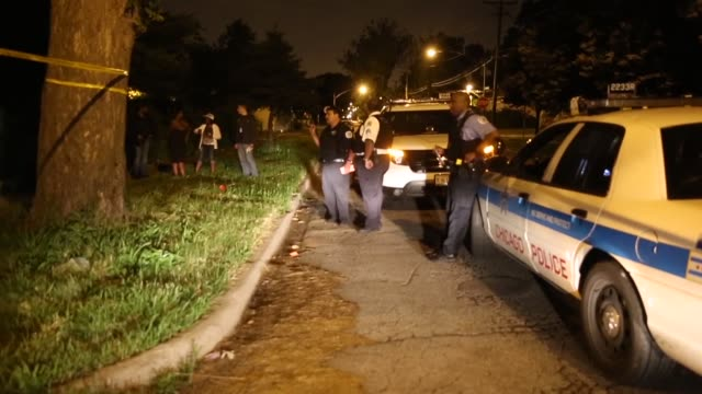 long shot of police officers at the crime scene. police collect evidence at the scene of a shooting on june 23, 2013 in chicago, illinois. a man was... - shooting crime stock videos & royalty-free footage