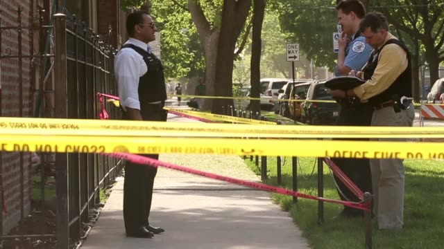 long shot of police officers investigating at the crime scene chicago gun violence crime scene on may 15 2013 in chicago illinois - gun crime stock videos & royalty-free footage