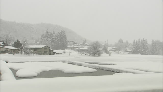 long shot of snow falling on miyama district, kyoto, japan - miyama kyoto stock videos & royalty-free footage