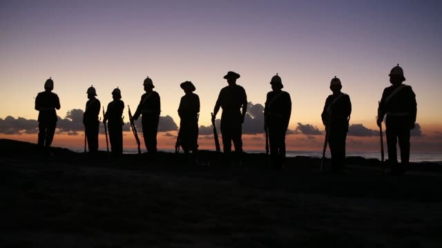 long shot of soldiers standing on the seashore with guns at dawn. australians commemorate anzac day on april 25, 2013 in various cities, australia... - anzac day stock videos & royalty-free footage