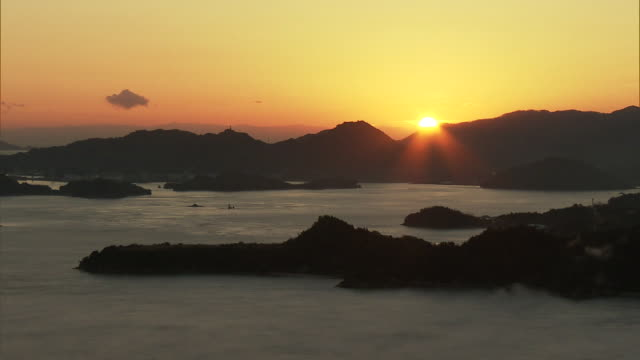 Long shot of sun rising behind a mountain under the reddish sky