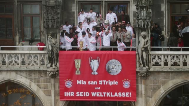 vidéos et rushes de long shot of the bayern muenchen team celebrating winning bundesliga champions league and dfb cup on the town hall balcony at marienplatz on june 2... - gagner