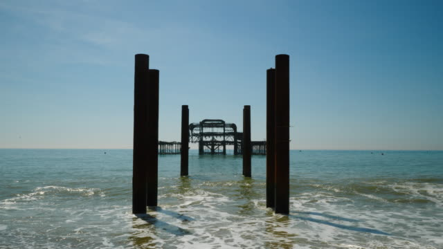 long shot of the derelict west pier on brighton beach, uk. - brighton england stock videos and b-roll footage