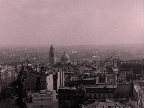 long shot of the eiffel tower. the camera pans left across the cities rooftops to the champs elysees. 1950's. - avenue des champs elysees stock videos & royalty-free footage