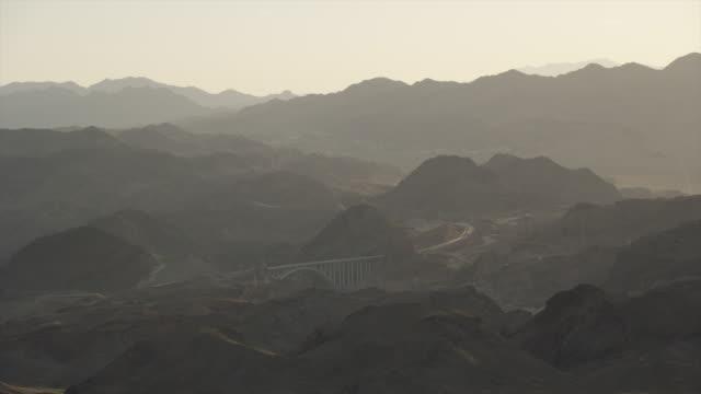long shot of the hoover dam through the haze and sunset - ネバダ州クラーク郡点の映像素材/bロール