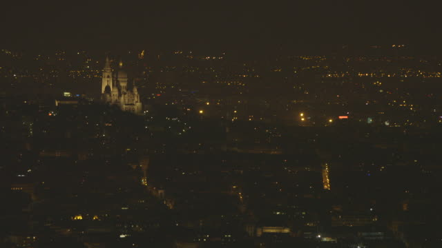 long shot of the illuminated area of montmartre (18th arrondissement) and beyond, including the sacré-cœur basilica, paris, france. - population explosion stock videos & royalty-free footage