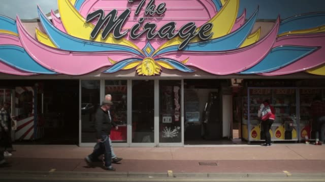 long shot of the mirage shopfront with classic cars passing by. fans of rock and roll, rockabilly, rockin' blues and americana gather at seacroft... - holiday camp stock videos & royalty-free footage