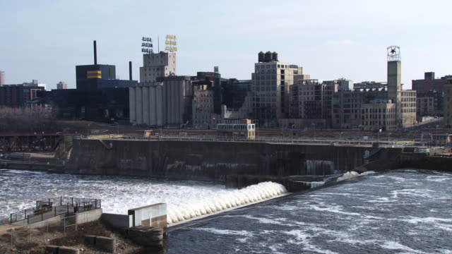 a long shot of the st. anthony falls, with some of the remaining buildings of the gold medal flour mill  - flour mill stock videos & royalty-free footage