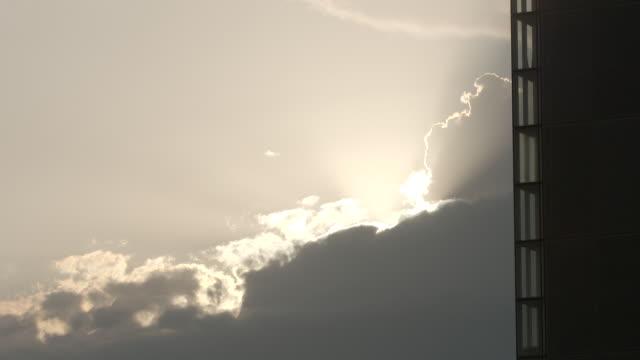 long shot of the sun breaking through the clouds behind the bibliothèque nationale de france - fönsterrad bildbanksvideor och videomaterial från bakom kulisserna