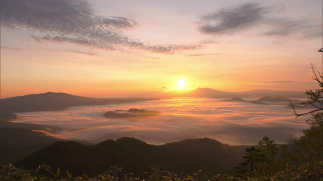 long shot of the sun just after sunrise and sea of clouds over lake kussharo lit up in orange after sunrise - stratus stock videos & royalty-free footage