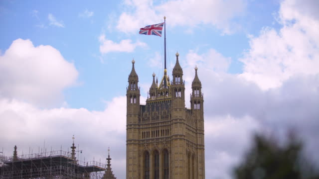Long shot of the Union flag flying from the top of Victoria Tower at the Palace of Westminster.