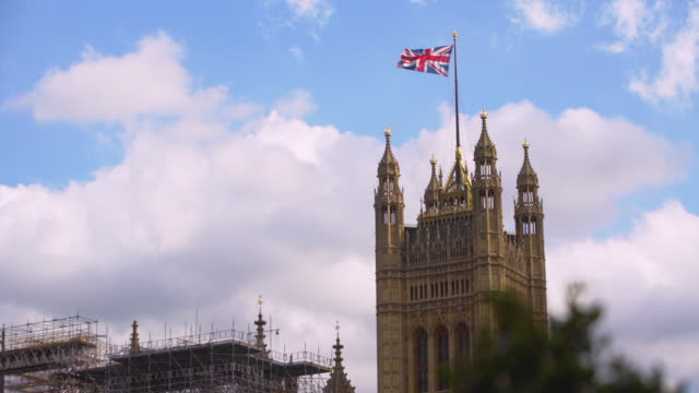 long shot of the union flag flying from the top of victoria tower at the palace of westminster. - bandiera del regno unito video stock e b–roll