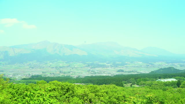 long shot of the village of minami-aso with homes dotted around the countryside, kumamoto, japan - satoyama scenery stock videos and b-roll footage
