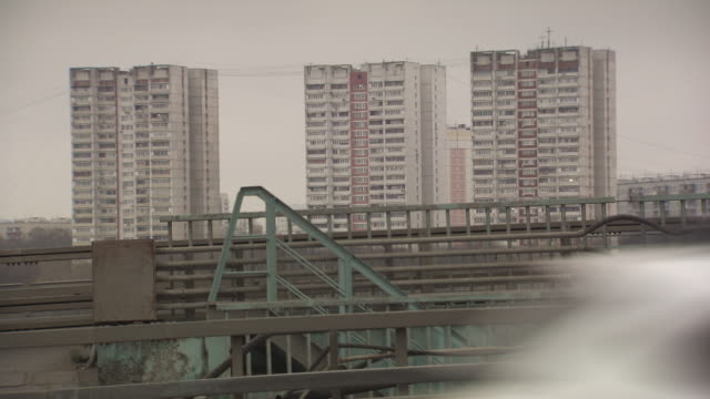 long shot of tower blocks near a busy road in moscow. - moscow russia stock videos and b-roll footage