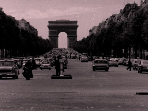long shot of traffic moving along the champs elysees with the arc de triomphe in the distance. 1950's. - avenue des champs elysees stock videos & royalty-free footage