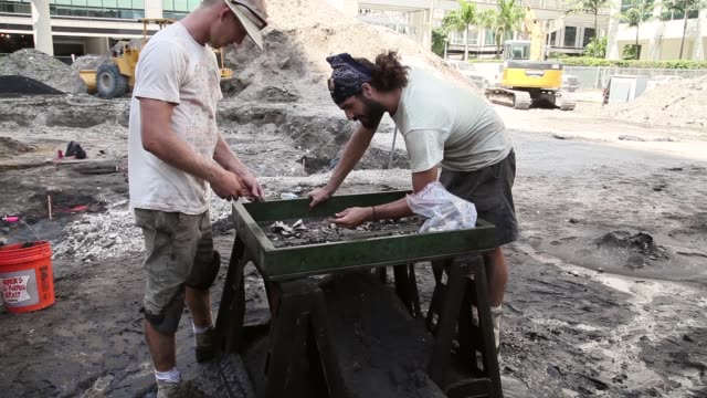 long shot of two archeologists sifting mud in search for artifacts archaeologists with the archaeological and historical conservancy work on... - baufahrzeug stock-videos und b-roll-filmmaterial