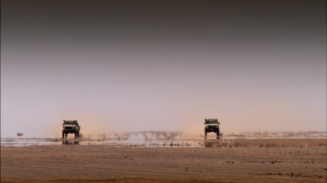 Long shot of two vehicles driving across the Western Sahara desert.