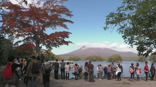 Long shot of visitors on the shore of lake Onuma
