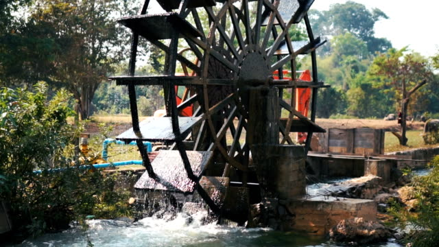 slo mo long shot of water wheel turning slowly through water - water wheel stock videos and b-roll footage