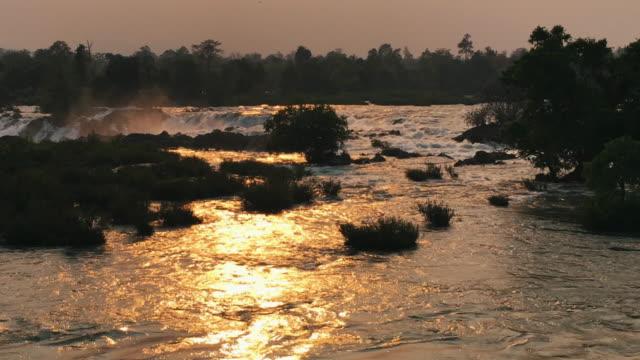 vídeos y material grabado en eventos de stock de largo tiro de cascadas con la puesta del sol se refleja en el agua - water plant