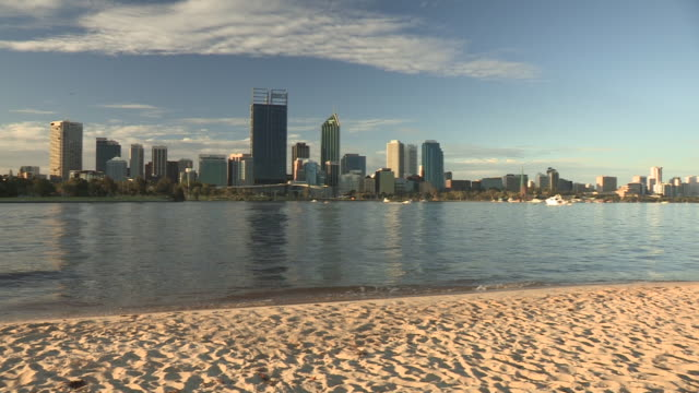 Long shot of waves gently rolling onto a sandy beach in Perth.