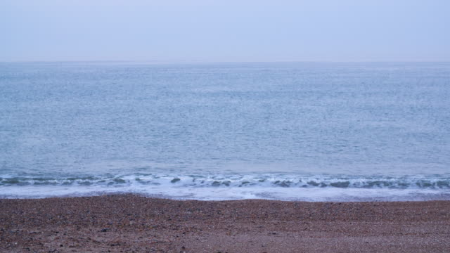 Long shot of waves rolling onto Brighton Beach at dawn.