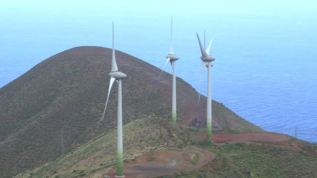 vídeos de stock, filmes e b-roll de long shot of wind turbines slowly turning on the island of el hierro. - hierro