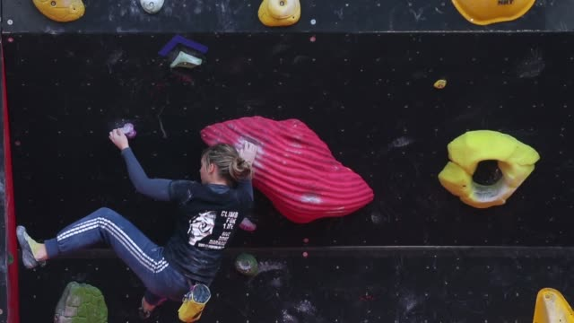 long shot of woman climbing up an artificial wall. long shot of woman climbing up an artificial wall. on april 05, 2013 in cortina d'ampezzo, italy - rock climbing stock videos & royalty-free footage