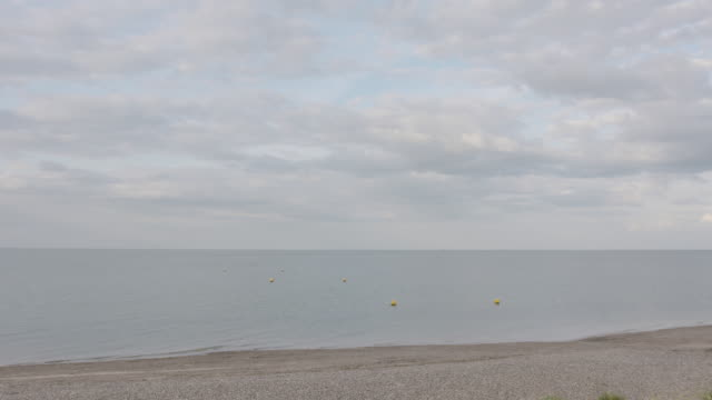 Long shot of yellow buoys floating off the coastline of northern Kent.