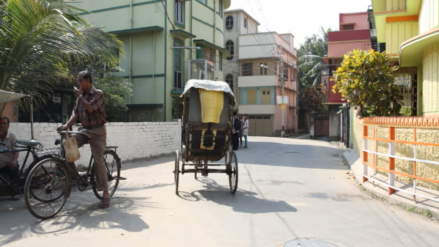 vidéos et rushes de long shot on a bicycle rickshaw driving along a street in kolkata the rickshaw driver is coming towards the camera passes the camera follows with a... - pousse pousse