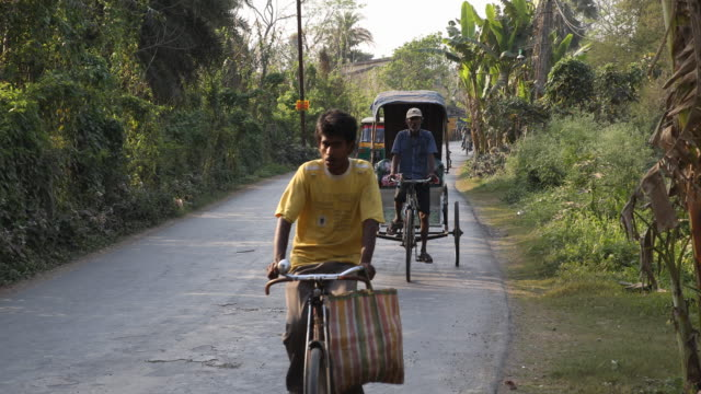 Long shot on a street outside Kolkata showing the traffic of cyclists and rickshaws