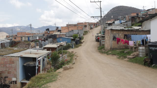 Long shot on an unpaved road of the slum with huts on its side and the mountains in the background showing a girl from afar walking up the road near...