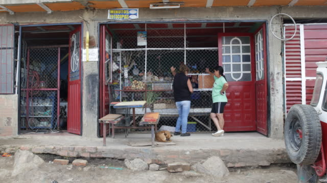 Long shot on eye level on a shop of the slum with a dog sleeping in front showing two women in front getting their goods purchased