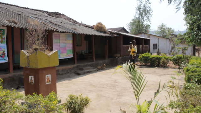 long shot on the school building with a young man holding a child on his arm in front, camera movement pan from right to left. - school child stock videos & royalty-free footage