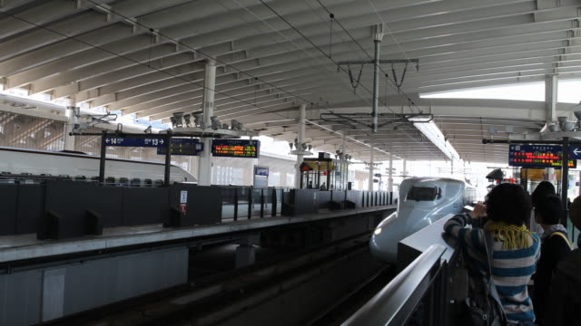 long shot on track 12 showing the arriving sakura express train while passengers are waiting on the platform - kyushu shinkansen stock videos and b-roll footage