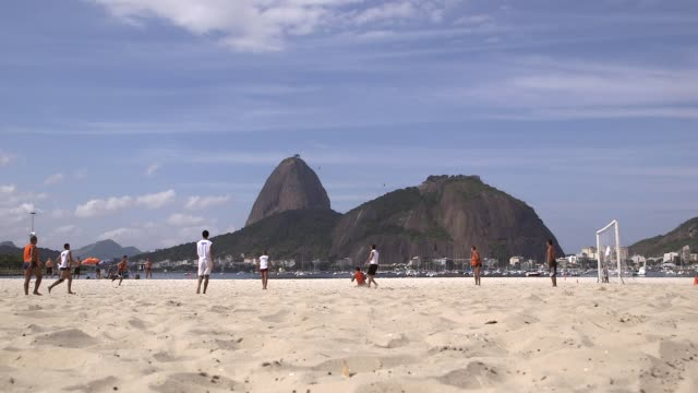 vídeos de stock, filmes e b-roll de long shot orange shirts goal kick amateur teams play play football on botafogo beach rio de janeiro brazil on june 9 2013 - baía de guanabara