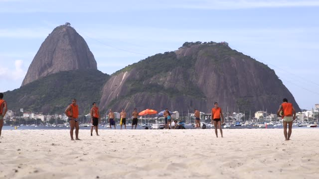 vídeos de stock, filmes e b-roll de long shot orange shorts free kick amateur teams play play football on botafogo beach rio de janeiro brazil on june 9 2013 - baía de guanabara