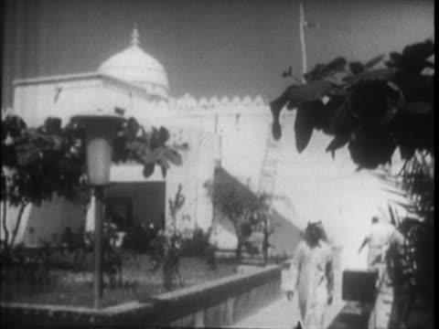 long shot palace walls and turret tilt up men walking down stairs to tower gardens with men walking on paths - シャイフ点の映像素材/bロール