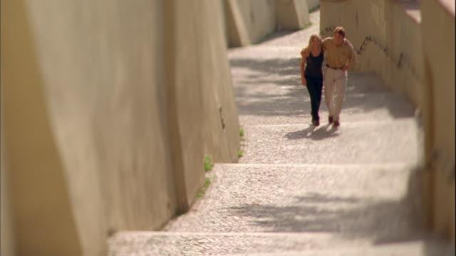 vídeos de stock, filmes e b-roll de long shot pan couple walking up outdoor steps / prague - de braços dados