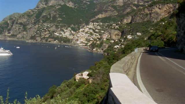 long shot pan from cars driving on coastal road to yacht off the coast of positano / amalfi coast, italy - coastal road stock videos & royalty-free footage