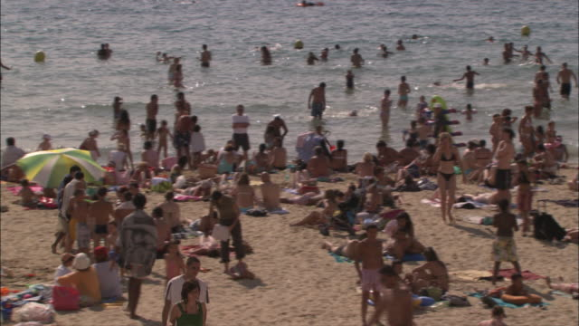 long shot pan right - mediterranean beach crowded with sunbathers and swimmers / marseille france - sunbathing stock videos & royalty-free footage