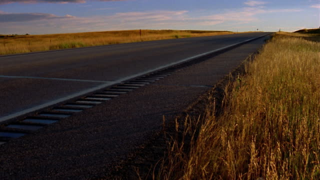 long shot pan tilt up from flat rural road to clouds and countryside / nevada - zaun stock-videos und b-roll-filmmaterial