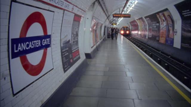 vídeos de stock e filmes b-roll de long shot pan train arriving at lancaster gate underground station / london, england - painel publicitário