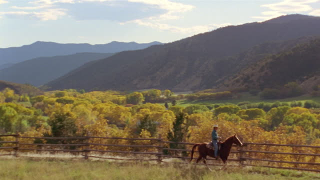 Long shot pan valley in autumn / man in cowboy hat riding horse along fence on ranch / Colorado