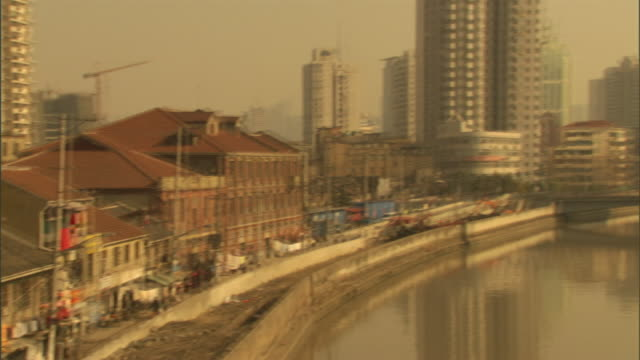 long shot pan-left tilt-down - a river flows through downtown shanghai and past a little market. / shanghai, china - 社会問題点の映像素材/bロール