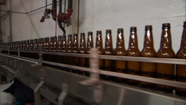 long shot pan-left tracking-left-beer bottles travel on conveyors through a brewery.   - bottling plant stock videos & royalty-free footage