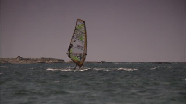long shot pan-right - a windsurfer rides waves on the mediterranean sea. / greece - tonad bild bildbanksvideor och videomaterial från bakom kulisserna