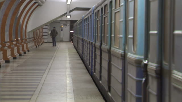 Long Shot pan-right - Passengers walk along a platform as a subway train pulls away. / Moscow, Russian Federation