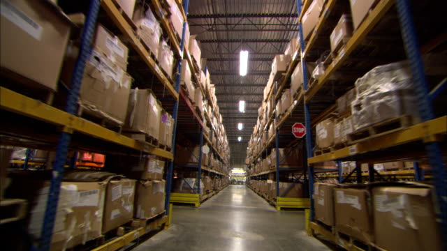 Long Shot pan-right push-in steadicam - Pallets of cartons are stacked on racks in a distribution warehouse